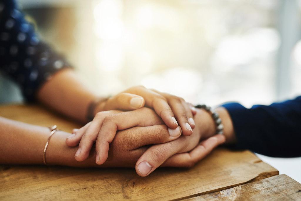 Mãos de pessoas unidas em uma ação de conforto