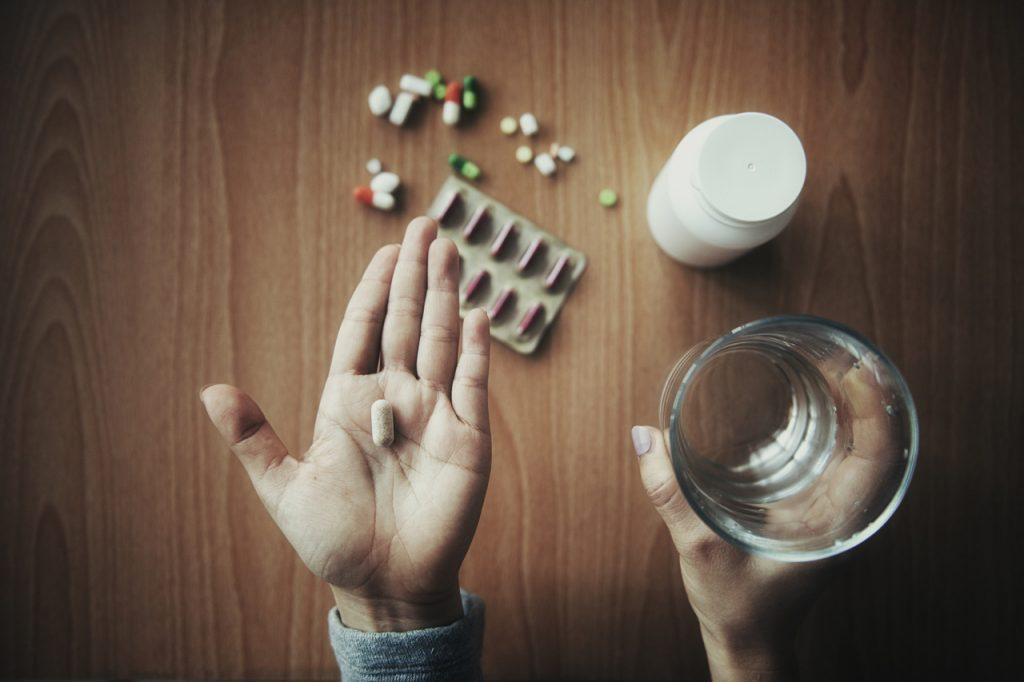 Mulher tomando medicamentos sem orientação médica