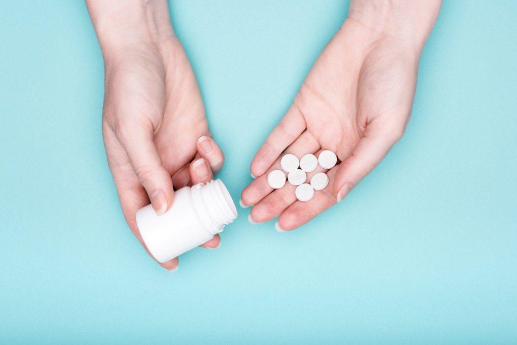 mãos femininas, segurando o frasco de medicação e pílulas brancas sobre fundo azul pastel